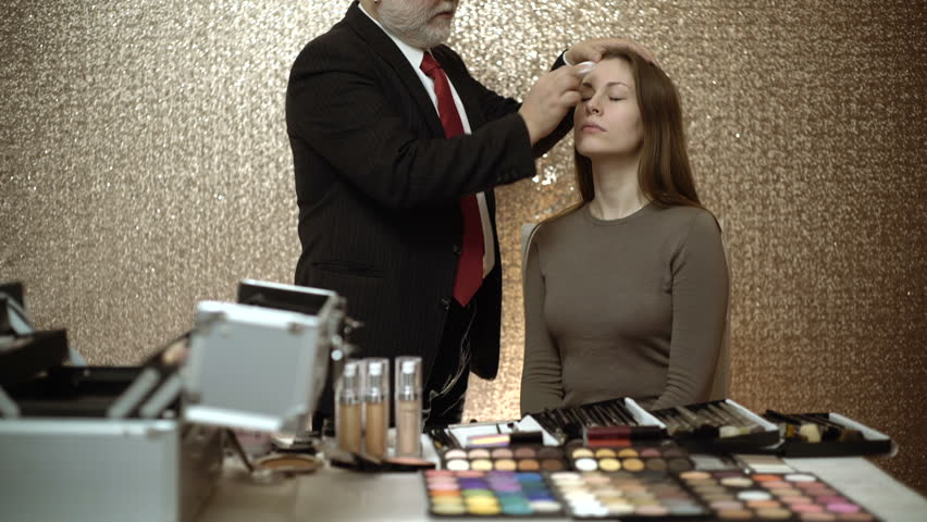 Professional makeup artist working with beautiful young woman. Professional makeup artist showing master classes for makeup.