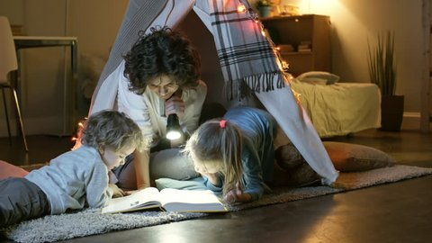 Tracking shot of loving mother and two little spending time together in cozy room at home and reading book in teepee tent at night