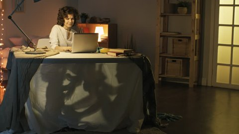 Tracking shot of smiling young woman working from home with laptop computer and looking after two little children playing under desk