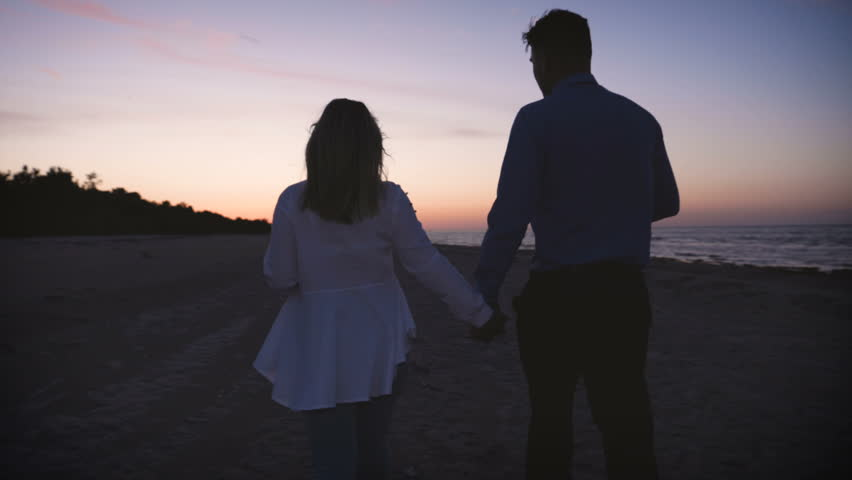 Young couple in love (guy and girl) are walking on the sea, holding hands, sunset, darkness. | Shutterstock HD Video #1012835990
