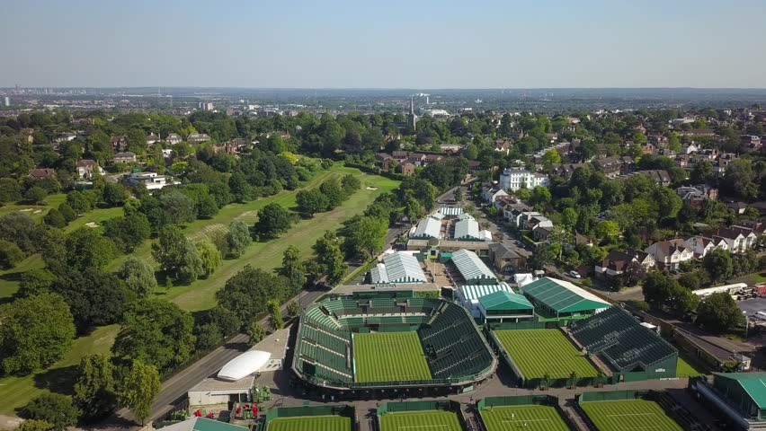 Aerial drone footage of the tennis stadium complex in Wimbledon, London, England on a bright sunny day.