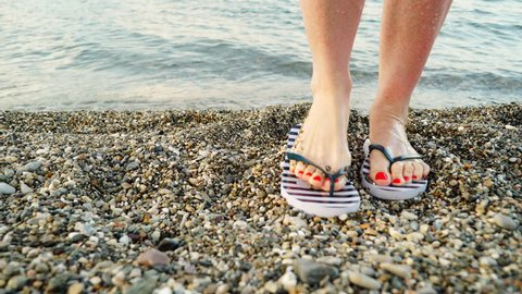 Woman feet red pedicure with blue striped flip flops summer shoes on sea shore stone beach. Holidays relax concept 4K.