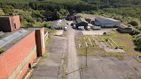 Aerial drone view flying towards the abandoned wheel and pit head at a disused coal mine (Tower Colliery)