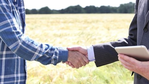 Close Up Of Businessman Shaking Hands With Farmer In Front Of Wheat Field