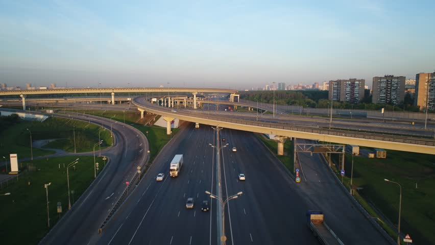 Aerial view. Flyght over a huge interchange of the Moscow ring road in the early morning at dawn. Cars are moving on a multi-level road junction. Urbanistic scenery. | Shutterstock HD Video #1012887470