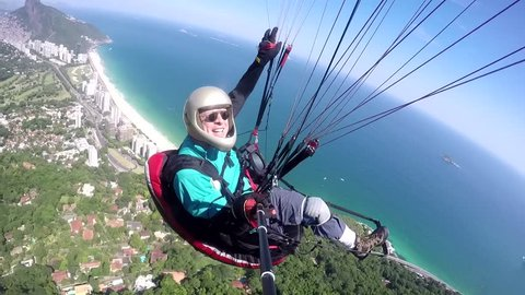 Paraglider pilot, physical handicapped, riding their own paragliding in Rio de Janeiro Brazil.