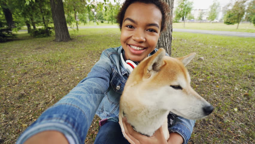 Point of view shot of pretty African American girl taking selfie with cute puppy in city park holding camera, smiling and posing. Modern technology and animals concept.