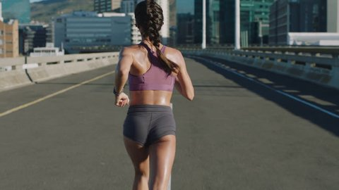 attractive young woman athlete running in city jogging exercising enjoying healthy fitness lifestyle female runner on sunny urban road rear view