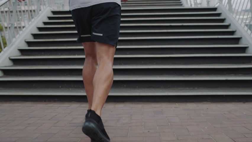 Young man legs running up stairs runner athlete feet jogging on steps training intense endurance workout in urban city background | Shutterstock HD Video #1012929020