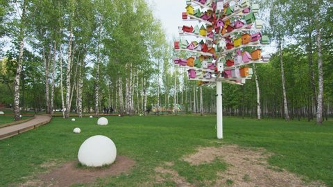 Funny Christmas tree construction covered with bright colored birdhouses on lawn among modern park