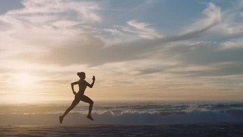 woman athlete silhouette running on beach sprinting waves crashing on seaside morning background slow motion