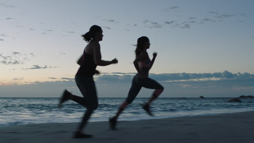 fit young woman athlete running overtaking in race competition female runners training intense cardio workout on beach at sunset background