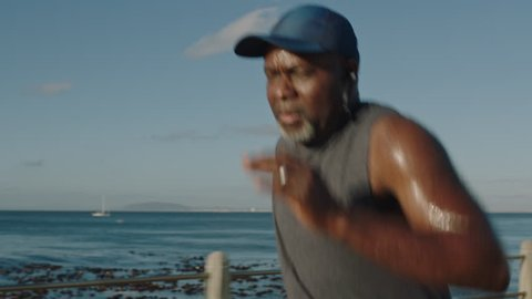 overweight african american man running black male runner exercising jogging healthy fitness workout lifestyle in ocean seaside background close up