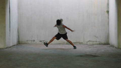 dancing man young talented street dancer breakdancing performing various freestyle dance moves fit mixed race male practicing in grungy warehouse