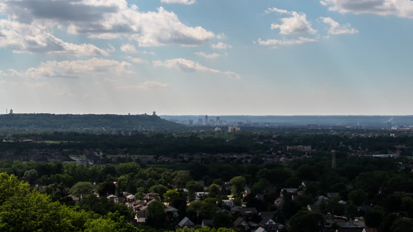 Time lapse of clouds over a cityscape during the summer time. Wide Establishing shot aerial view of a city skyline. Time lapse overlooking homes and buildings in the city. | Shutterstock HD Video #1012955210