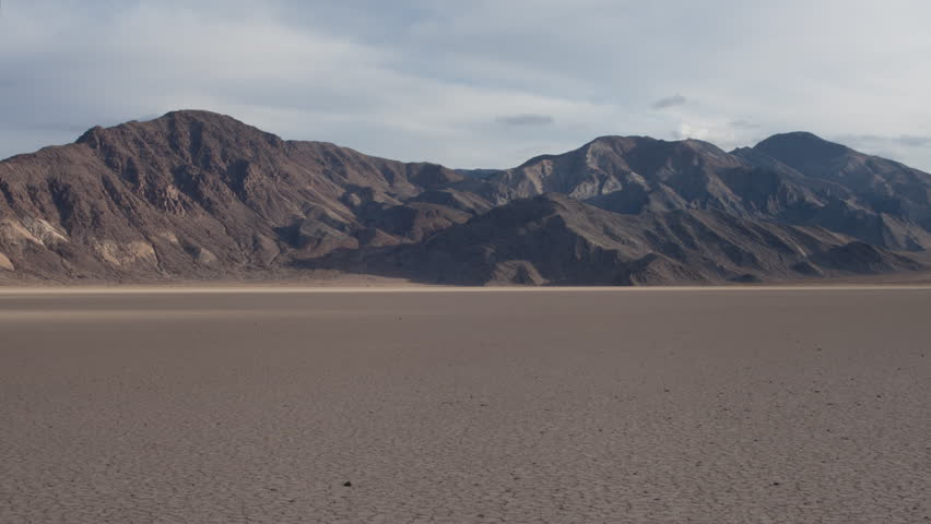 4K time lapse of clouds and cloud shadows moving across distant rocky desert hills and the desert Racetrack dry lake bed in Death Valley National Park, California on a mostly cloudy afternoon