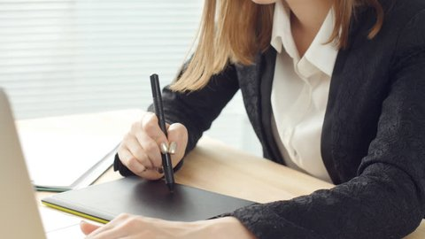 Woman designer working in office with graphic tablet