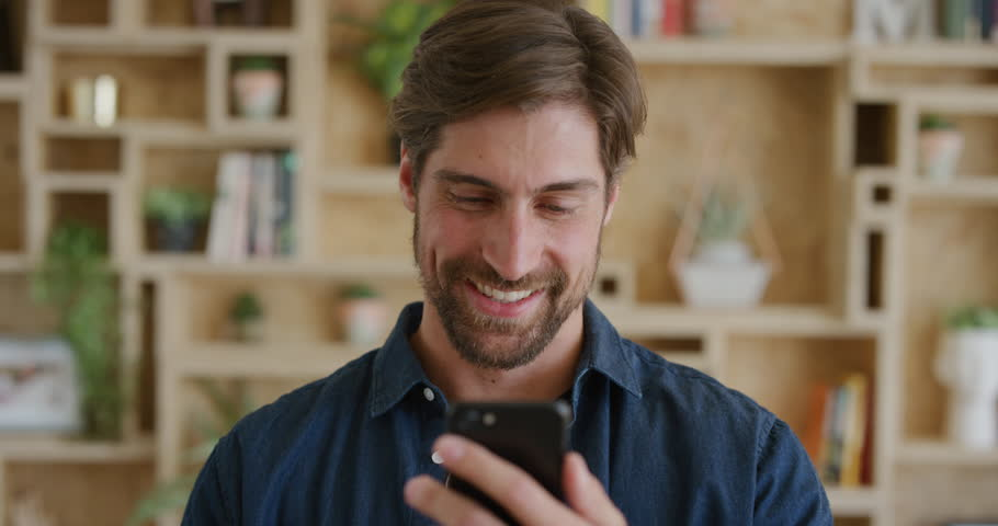 portrait of handsome young man using smartphone texting browsing enjoying mobile communication on cellphone technology in modern home background slow motion #1012994030