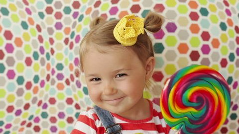 Cute funny girl 3.5 years old licking a big lollipop