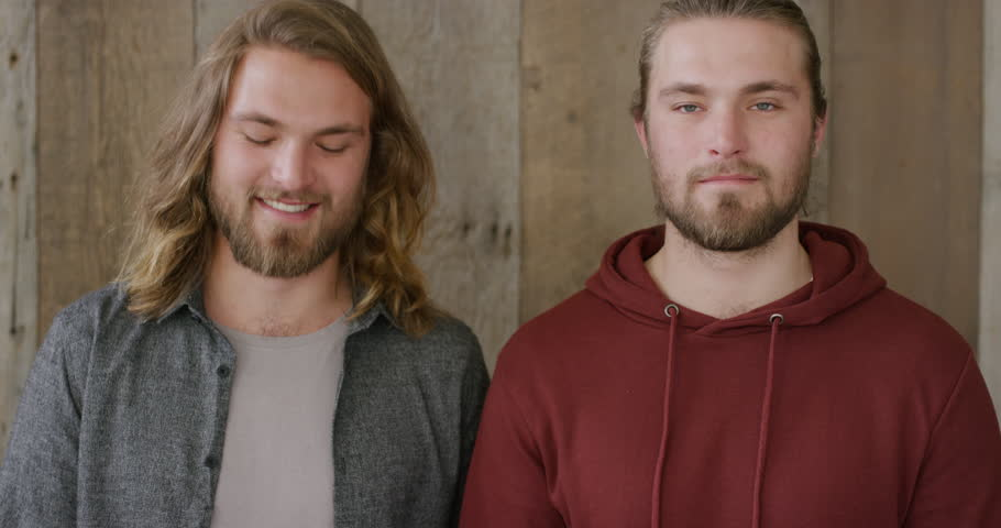 Portrait of attractive twin brothers using smartphone browsing enjoying sharing mobile technology communication together smiling happy siblings family connectedness | Shutterstock HD Video #1013001830