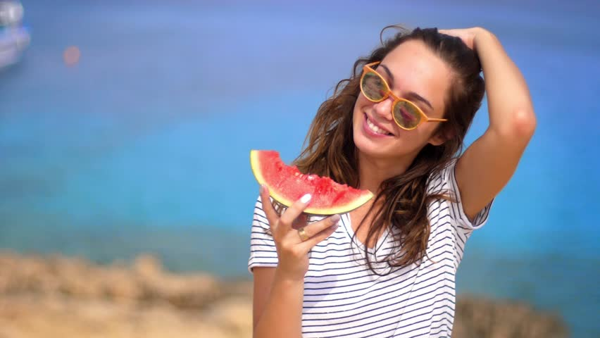 Smiling woman eating watermelon on beach in slow motion. Happy summer time. Portrait of happy woman eat watermelon on beach. Female emotion at summer vacation. Female tourist eating tasty summer fruit