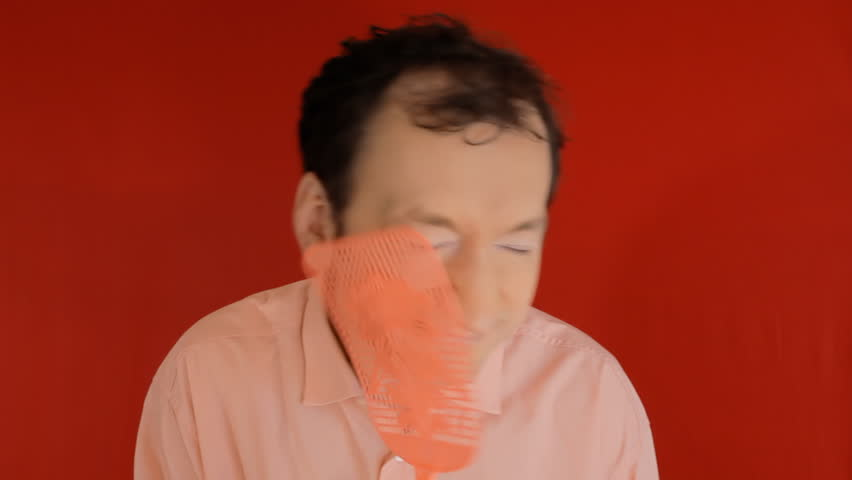 A funny ugly man trying to kill a fly with a swatter, but ending up hitting himself on the face. Red background.