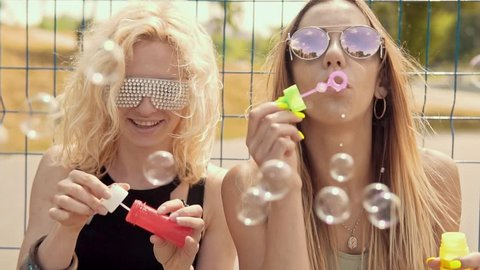 Cheerful hipster girls in sunglasses having fun making bubbles outdoors in slow motion. Close up