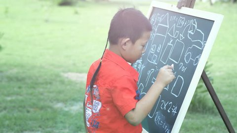 Asian boy with creativity, learn math, drawing, School Boy Ideas on black chalk board.  green nature background. concept of learning, educational outings.
