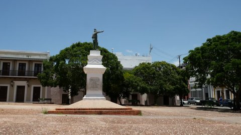 Old San Juan, Puerto Rico - June 2018: Plaza San Jose Square with statue of Juan Ponce de Leon a spanish conquistador and colonial buildings in background - 4k unmodified camera native file