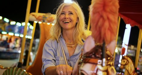 Happy fashionable senior woman on summer vacations having fun on funfair merry-go-round ride at night