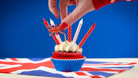 Red white and blue theme cupcake with candles and UK Union Jack flags for Queen's Birthday weekend celebration or Great Britain party food.