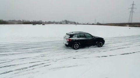 Black SUV drifting on a snow track. A lot of snow.