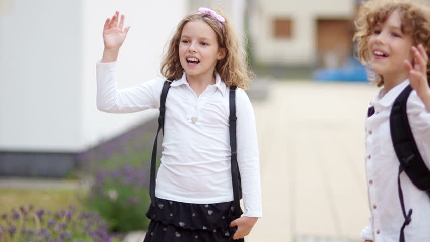 A pair of curly schoolchildren, a boy and a girl, say goodbye, waving their hands, looking at the camera, unfolding and leaving. Goodbye school, back to school   Shutterstock HD Video #1013043170