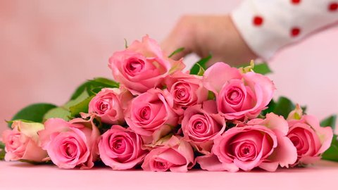 Woman placing pink roses on pink wood table, Mother's Day background closeup.