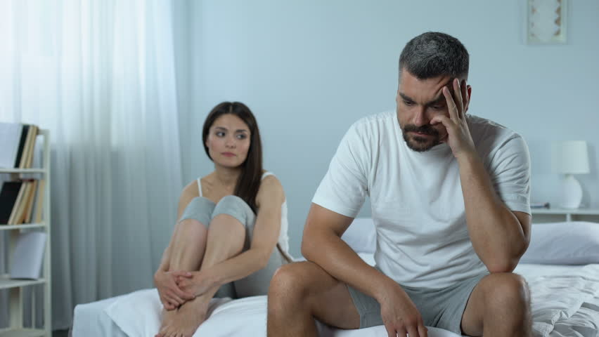 Man suffering problems with masculine health, wife supporting him, impotence