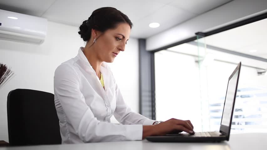Young brunette female business woman working on a laptop in a boardroom clean white modern environment smiles after finishing work and looks at camera | Shutterstock HD Video #1013085560