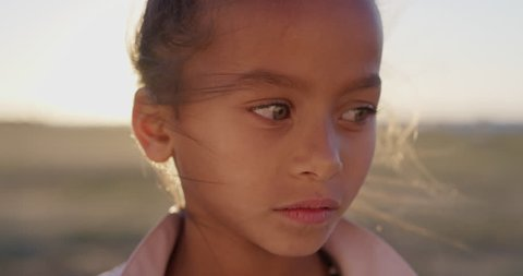close up portrait young little mixed race girl looking serious contemplative kid on sunny park sunset real people series