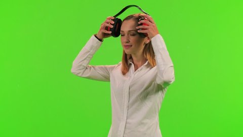 A woman puts an earmuffs on her ears, over a green screen, 3 takes.
