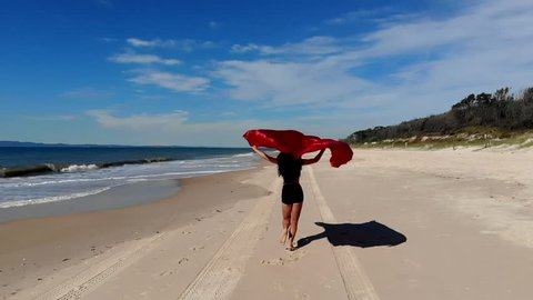Drone Footage. Tracking and Pedestal shots. Woorim Beach, Bribie Island. A woman in a bikini runs away from the camera on a deserted beach holding a red satin sheet above her head in slow motion.