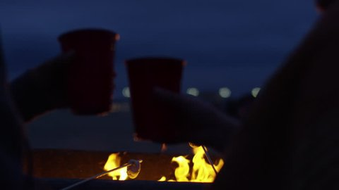 Friends Roast Marshmallows And Cheers With Beer At Beach, Lights From Boardwalk Shine In Distance (Slow Motion)
