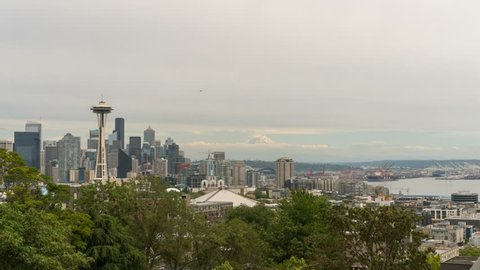 Timelapse movie of gray sky and clouds over urban scenic view of Seattle Washington cityscape and Mount Rainier and seaport 4k UHD