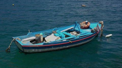 Small fishing boat in Greece bobbing in the sea.