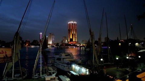 CAIRO, EGYPT - DECEMBER 23, 2017: Evening on Corniche embankment of Nile river, illuminated high-rises of Gezira Island are seen behind felucca boats, moored at small shipyard, on December 23 in Cairo