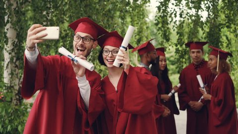 Cheerful couple of graduating students is taking selfie using smartphone, young man and woman are holding diplomas, looking at smart phone camera and smiling.