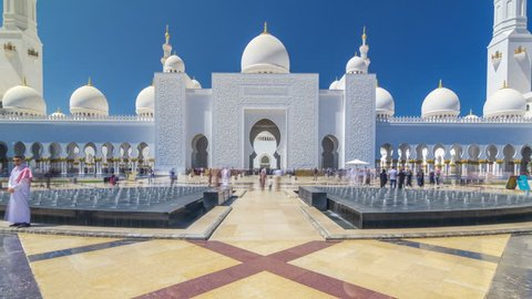 Sheikh Zayed Grand Mosque timelapse hyperlapse in Abu Dhabi, the capital city of United Arab Emirates. Front view with fountains. Blue sky at sunny day