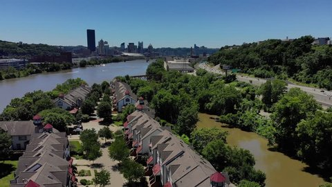 A high angle reverse aerial flyover of the upscale homes on Washington's Landing, an island on the Allegheny River just outside of Pittsburgh. City skyline in the distance.