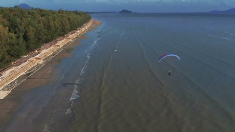 Close up paramotor flies along the sandy beach. The coast of Thailand. Trang province. Sikao. Paraglide. Para motor