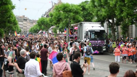STRASBOURG, FRANCE - JUN 10, 2017: Large crowd waving LGBT flags at gay pride parade with thousands of people dancing on the street - elevated view with gay truck