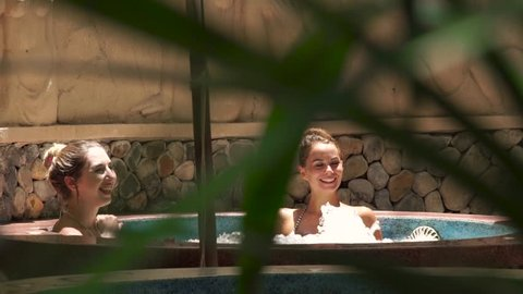 Happy woman taking jacuzzi bath in luxury spa center. Smiling woman relaxing and enjoying bathing in jacuzzi spa for body care. Skin care and body therapy. Beauty concept