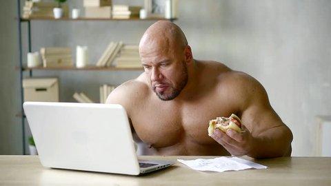 Shirtless weghtlifter holding fat junky hamburger while reading something online.